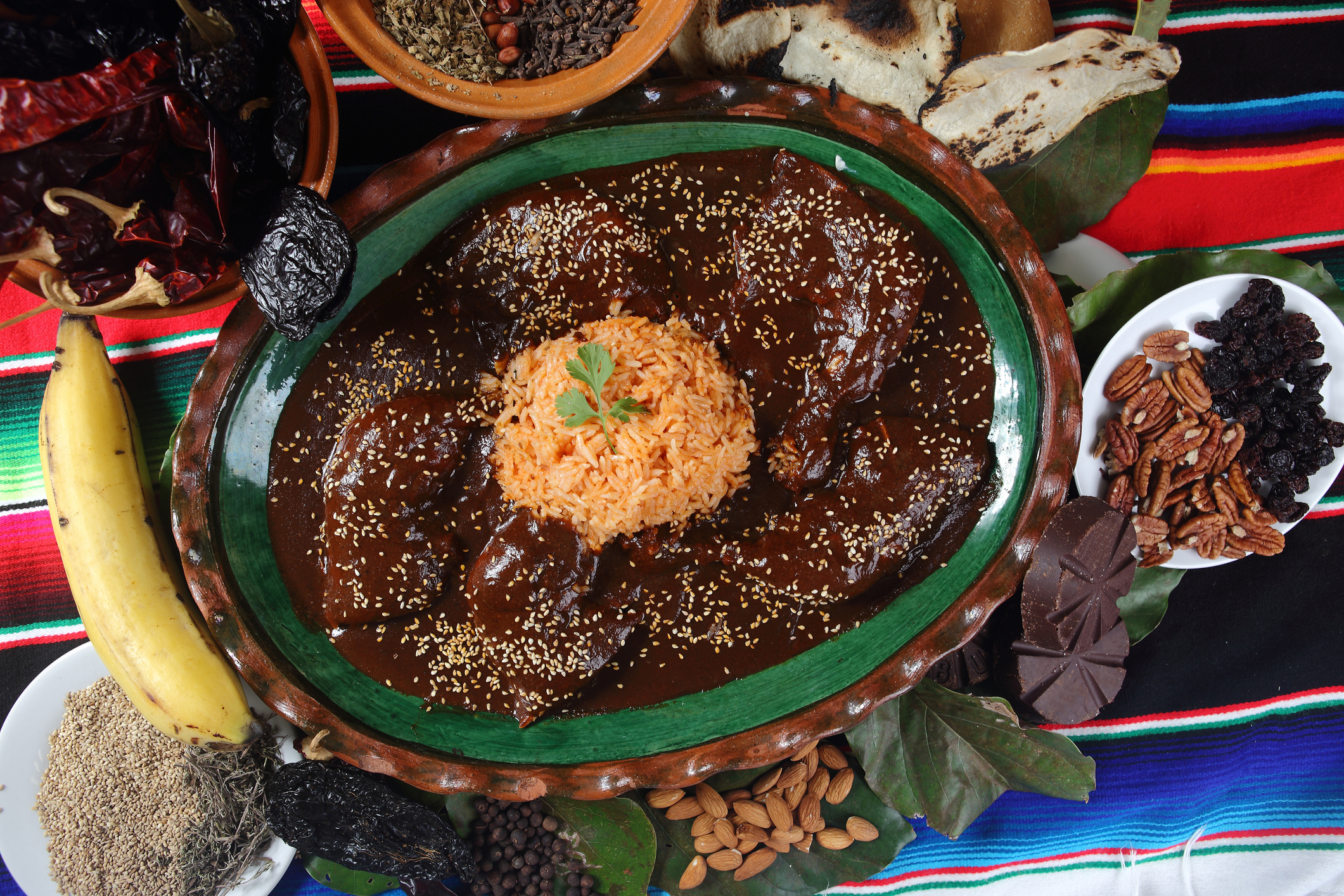 Chicken mole with sesame accompanied by steamed rice and served on clay plates.